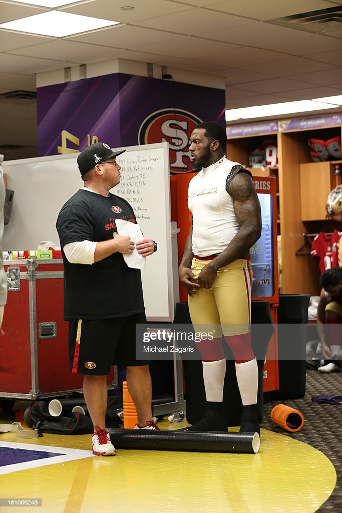 Head Strength and Conditioning Coach Mark Uyeyama of the San Francisco 49ers talks with Patrick Willis #52 in the locker room prior to Super Bowl XLVII against the Baltimore Ravens at the Mercedes-Benz Superdome on February 3, 2013 in New Orleans, Louisiana. The Ravens won 34-31.