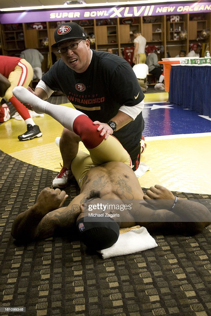 Head Strength and Conditioning Coach Mark Uyeyama of the San Francisco 49ers stretches NaVorro Bowman #53 in the locker room prior to Super Bowl XLVII against the Baltimore Ravens at the Mercedes-Benz Superdome on February 3, 2013 in New Orleans, Louisiana. The Ravens won 34-31.