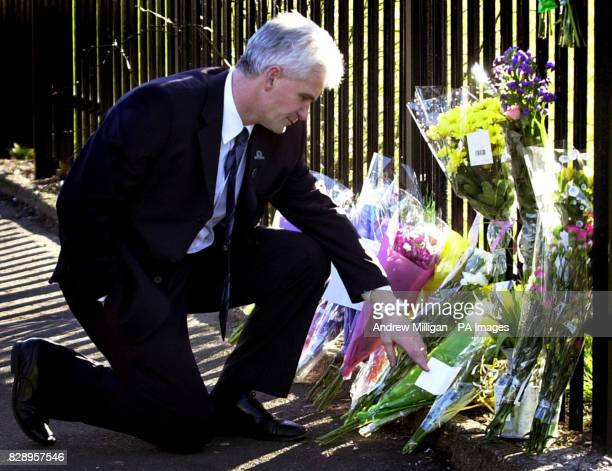 Head Teacher Tom McDonald looks at flowers left at the gates of all Saints RC Secondary School in Glasgow where elevenyearold Suhail Saleh died after...