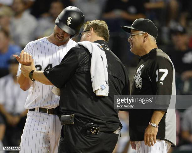 Head trainer Herm Schneider inspects the wrist of Matt Davidson as manager Rick Renteria of the Chicago White Sox looks on after Davidson was hit by...
