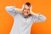 Headache. Human pain concept. Businessman sick. Studio shot, orange background