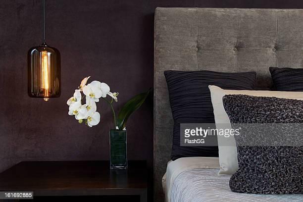 Détail de la tête de lit et oreillers moelleux, d'une lampe et des orchidées