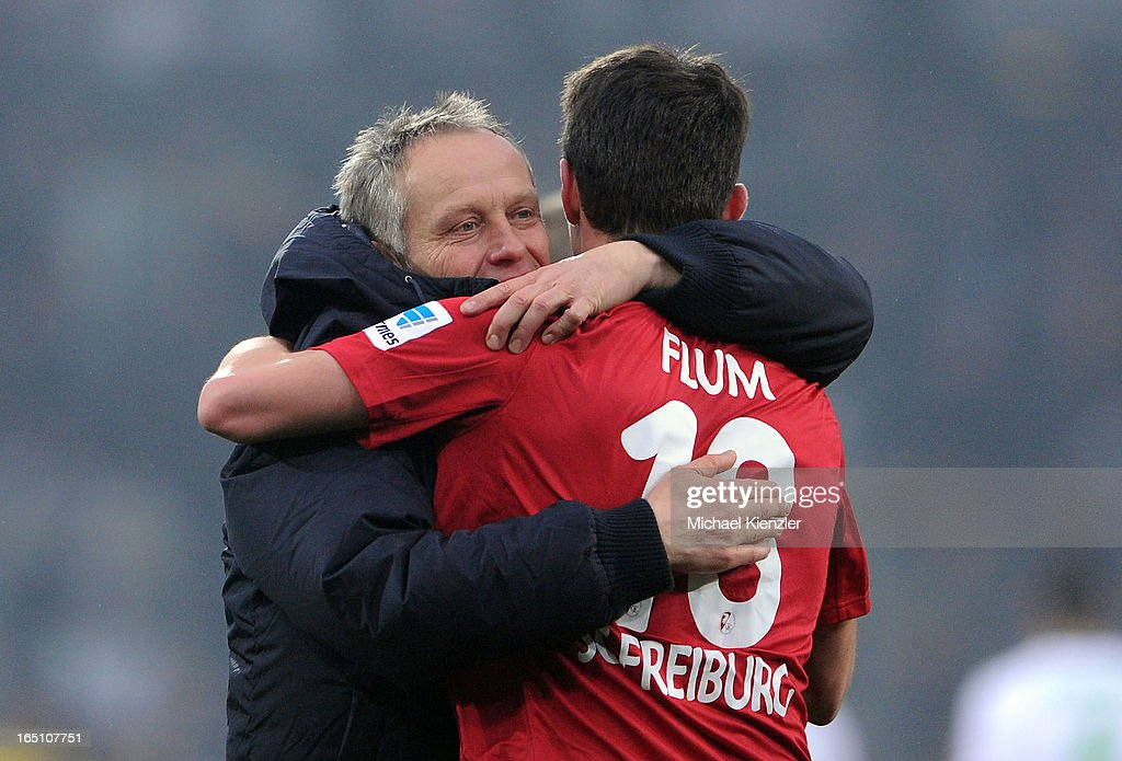 Headcoach Christian Streich of Freiburg (L) hugs Johannes Flum after the Bundesliga match between SC Freiburg and VfL Borussia Moenchengladbach at MAGE SOLAR Stadium on March 30, 2013 in Freiburg, Germany.