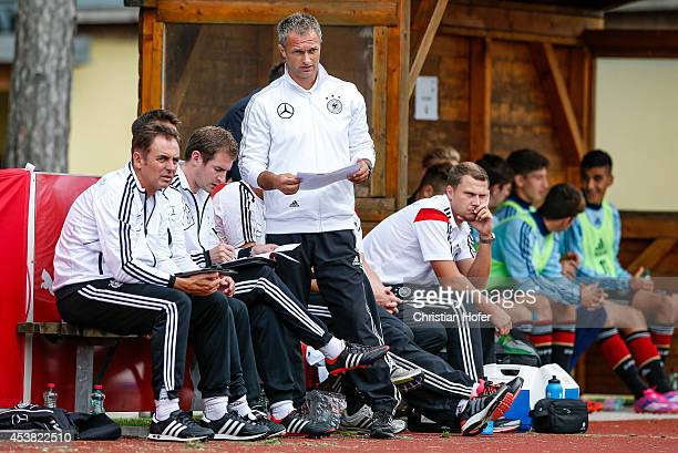 Headcoach Christian Wueck of Germany stands between staff members watching the TOTO Cup match between U17 Germany and U17 Switzerland on August 19...