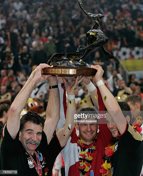 Headcoach Heiner Brand Keeper Henning Fritz and Markus Baur of Germany llift the World Cup trophy following the victory over Poland in the IHF World...