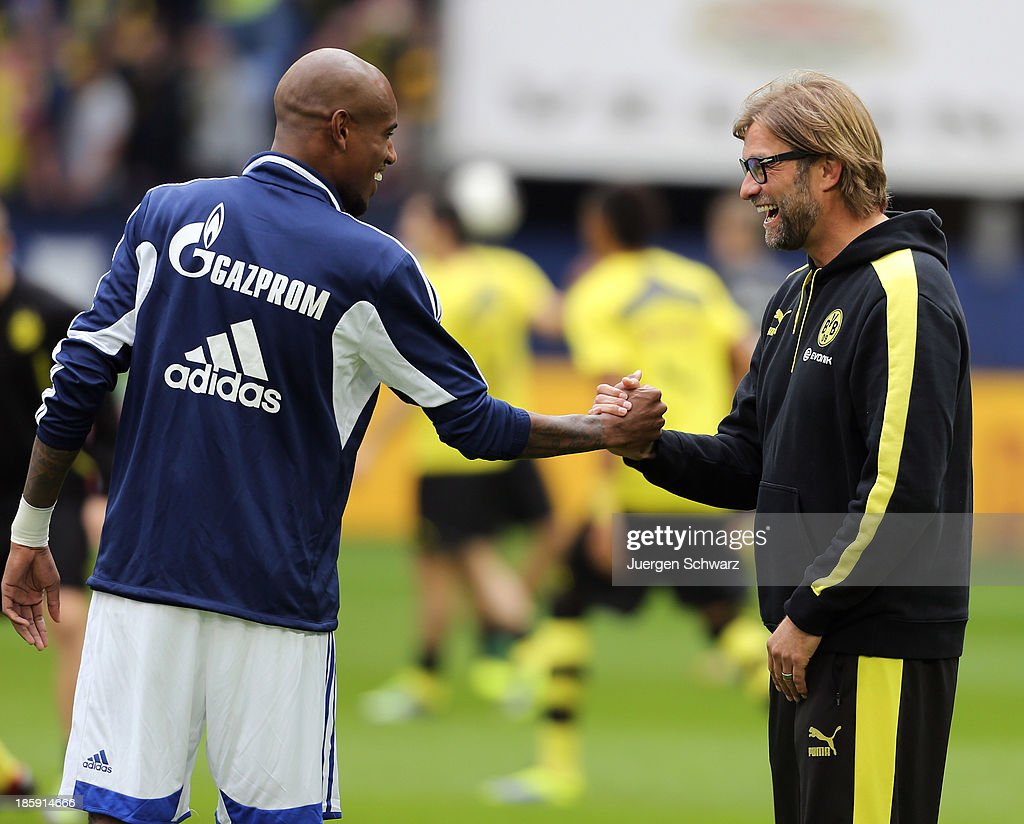 Headcoach Juergen Klopp of Dortmund (R) shakes hands with Felipe Santana of Schalke during their teams warm up at the Bundesliga match between Schalke 04 and Borussia Dortmund at Veltins-Arena on October 26, 2013 in Gelsenkirchen, Germany.