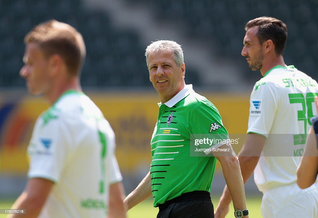 Headcoach <a gi-track='captionPersonalityLinkClicked' href=/galleries/search?phrase=Lucien+Favre&family=editorial&specificpeople=4313368 ng-click='$event.stopPropagation()'>Lucien Favre</a> (C) smlies on his way to the team presentation of Borussia Moenchengladbach on July 9, 2013 in Moenchengladbach, Germany.