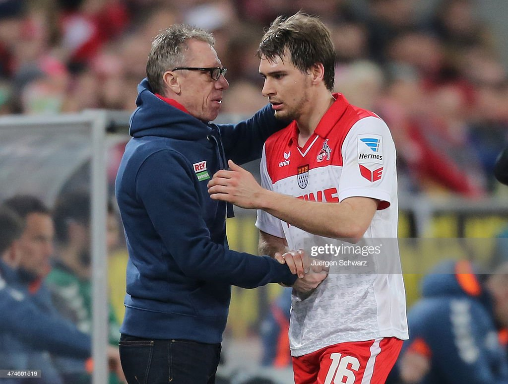 Headcoach Peter Stoeger of Cologne (L) hugs Patrick Helmes who leaves the pitch during the 2nd Bundesliga match between 1. FC Koeln and Greuther Fuerth at RheinEnergieStadion on February 24, 2014 in Cologne, Germany.