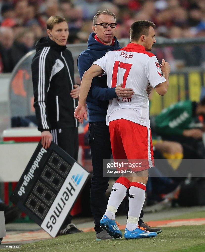 Headcoach Peter Stoeger of Cologne (L) hugs Slawomir Peszko during the 2nd Bundesliga match between 1. FC Koeln and Greuther Fuerth at RheinEnergieStadion on February 24, 2014 in Cologne, Germany.