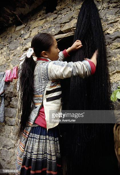 A headdress is prepared by a member of the Miao ethnic minority group in their village September 1993 in Guizhou Province China The Miao are a...