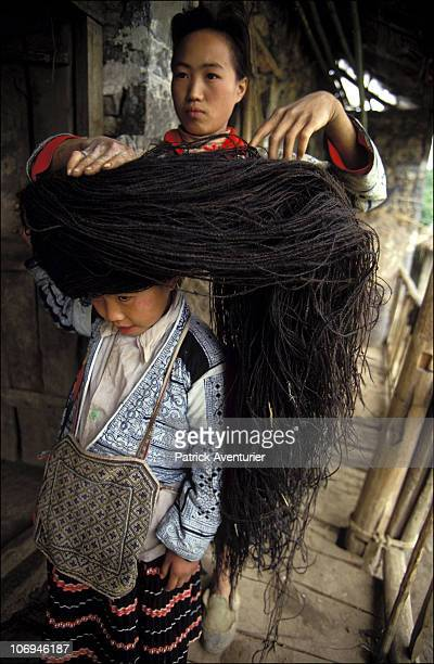 A headdress is prepared by members of the Miao ethnic minority group in their village September 1993 in Guizhou Province China The Miao are a...