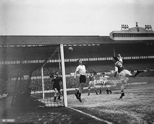 A header by Arsenal centreforward Len Julians rebounds off the crossbar as Tottenham Hotspur rightback Peter Baker tries to intercept with Spurs...
