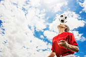 Soccer player heading the ball against the sky. Copy space.