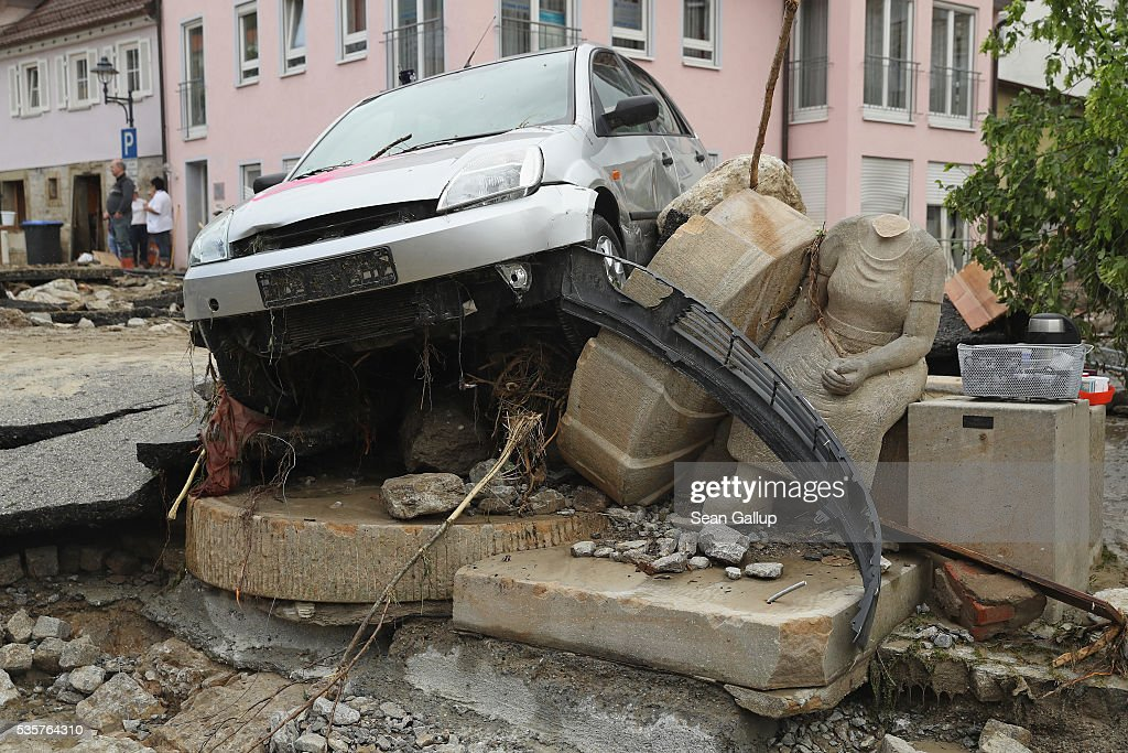 A headless monument and smashed car stand in the village center following a furious flash flood the night before on May 30, 2016 in Braunsbach, Germany. The flood tore through Braunsbach, crushing cars, ripping corners of houses and flooding homes during a storm that hit southwestern Germany. Miraculously no one in Braunsbach was killed, though three people died as a result of the storm in other parts of the country.