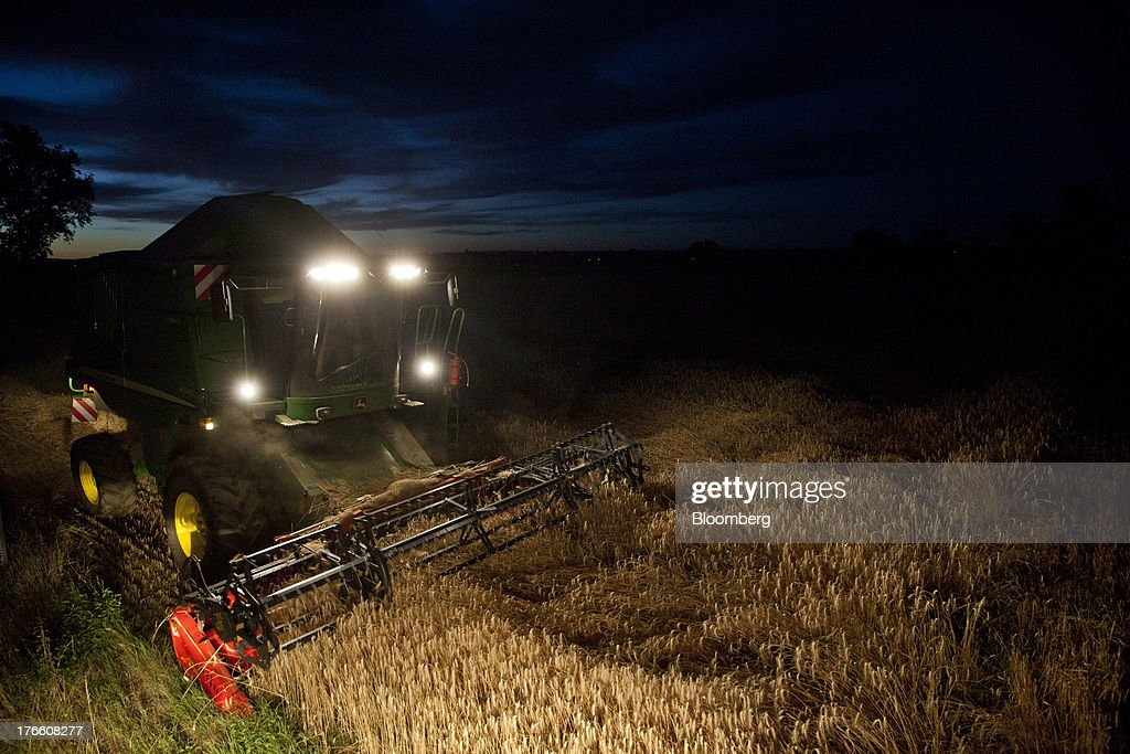 Headlights illuminate a field as a Deere & Co. John Deere W540 combine harvester gathers crops in a field of triticale wheat, in Falguieres, southwest France, on Thursday, Aug. 15, 2013. French farmers harvested better-quality wheat than expected north and east of Paris, making up for low protein content in the southwest and raising confidence the grain will meet export requirements. Photographer: Balint Porneczi/Bloomberg via Getty Images