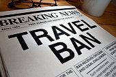 TRAVEL BAN Headline on a newspaper. Newspaper is on a desktop.