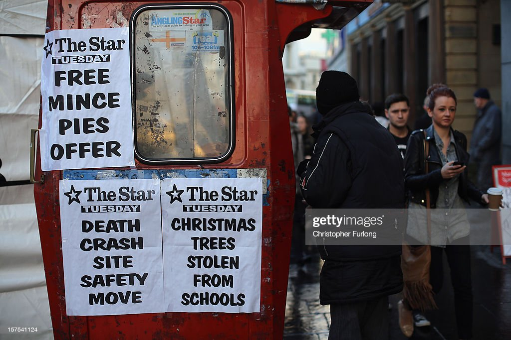 Headlines adorn a booth as a vendor sells newspapers on December 4, 2012 in Sheffield, United Kingdom. Retailers across Britain are struggling as people wait for bigger discounts before spending for the Christmas period. The British Retail Consortium (BRC) said that it's members were in a 'state of nervousness' in the last weeks of the festive period.