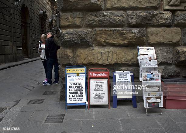 Headlines from La Nazione La Repubblica and other daily newspapers printed on sheets of paper and displayed on racks promote newspaper sales at a...