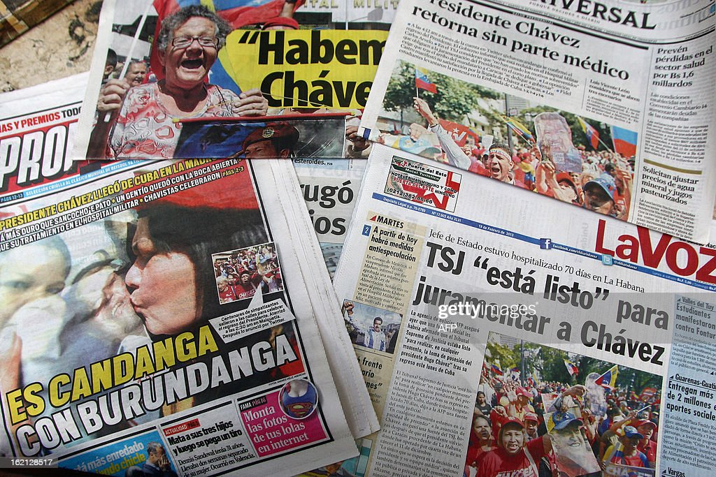 Headlines of newspapers inform about the arrival of Venezuelan President Hugo Chavez at the country, in Caracas on February 19, 2013. President Hugo Chavez returned to Venezuela early on February 18 after spending more than two months in Cuba for cancer surgery and treatment, announcing his surprise homecoming via Twitter. AFP PHOTO/GERALDO CASO