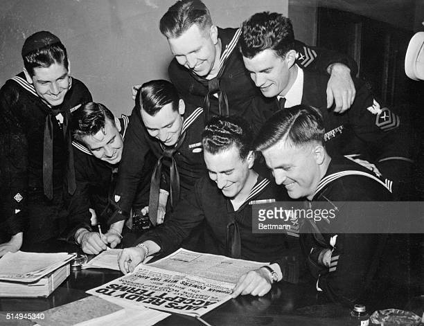 Headlines proclaiming Japans' readiness to accept surrender terms bring wide grins to the faces of these seven Navy men reading the good news in a...