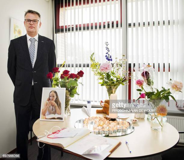 Headmaster Jan Hofmann poses next to a table with a book of condolence flowers and candles for killed 14yearold girl Romy Nieuwburg at the JH Donner...