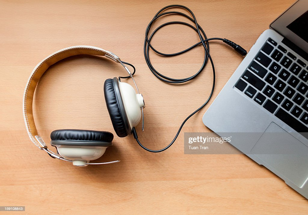 Headphones connected to laptop : Stock Photo