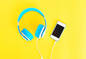 Headphones connected to white smartphone on a yellow background