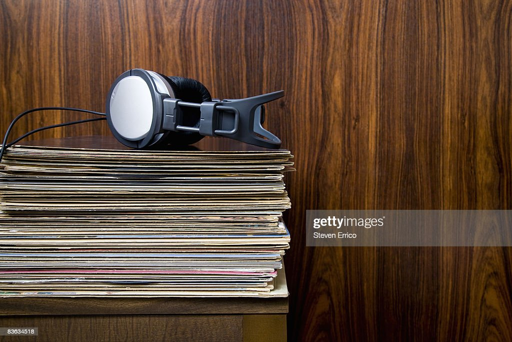Headphones laying on stack of vinyl records : Stock Photo
