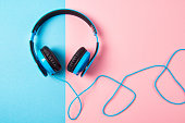 Modern blue Headphones on blue and pink background, top view
