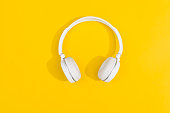 White wireless headphones on yellow background