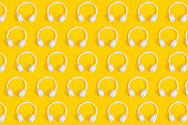 Repetitive pattern of white wireless headphones on yellow background