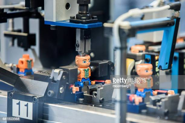 Heads are affixed to Lego Duplo toy figurines on the production line at the Lego A/S plant in Nyiregyhaza Hungary on Tuesday May 9 2017 After turning...