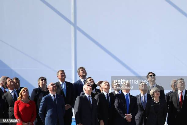 Heads of state including US President Donald Trump and British Prime Minister Theresa May stand to watch a military flypast during the NATA Summit...