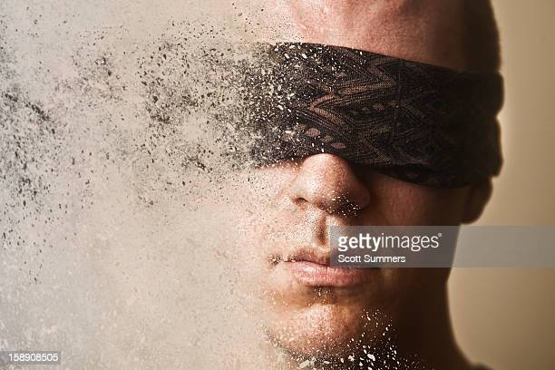 Headshot of a blindfolded man disintegrating.