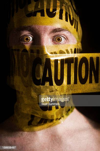Headshot of a man wrapped in caution tape.