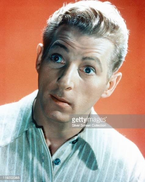 Headshot of a wideeyed Danny Kaye US actor singer dancer and comedian in a studio portrait against an orange background circa 1945