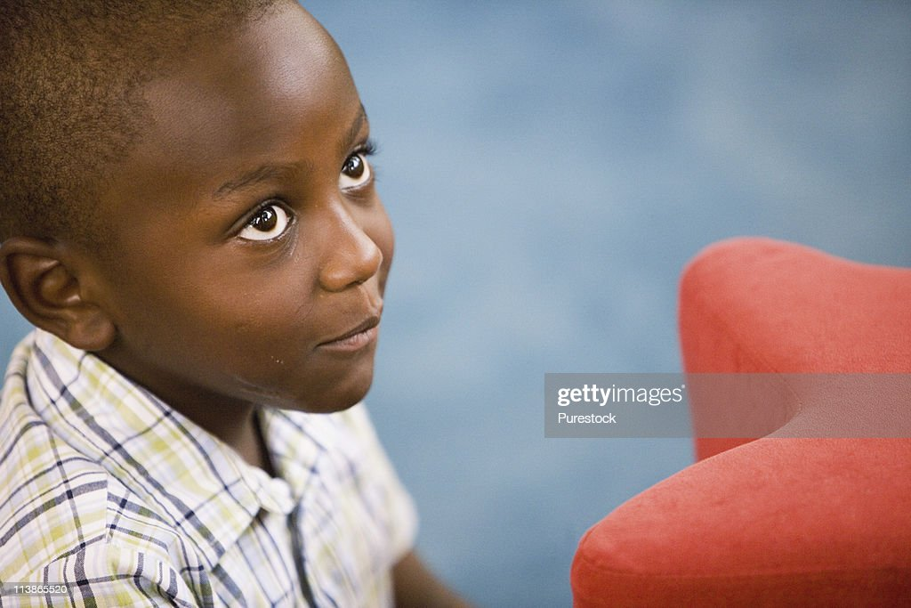 Head-shot of a young boy in a colorful room : Stock Photo