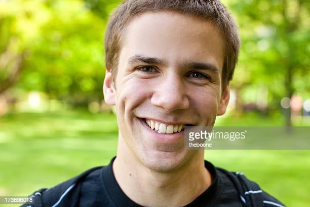 Photo d'un jeune homme souriant à la caméra dans le parc