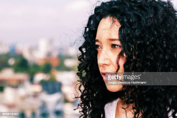 Headshot of a young woman with very curly hair in Mexico City