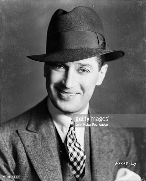 Headshot of actor Maurice Chevalier wearing a hat and checked tie for Paramount Pictures 1932
