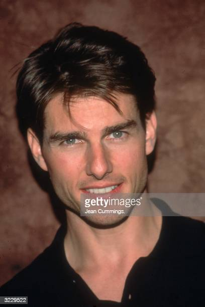 Headshot of American actor Tom Cruise smiling in a black shirt in front of a brown backdrop