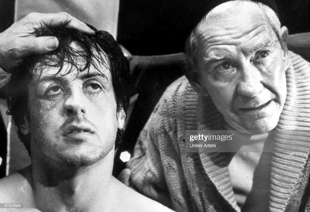 1976, Headshot of American actors Sylvester Stallone (left) and Burgess Meredith (1909 - 1997) in a still from the boxing film 'Rocky' directed by John Avildsen.