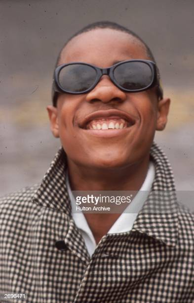 Headshot of American musician Stevie Wonder smiling in a black and white checkered jacket and sunglasses