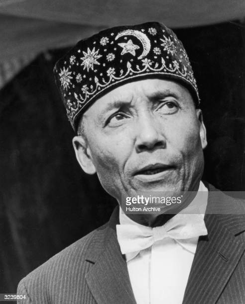 Headshot of American religious leader Elijah Muhammad leader of the Black Muslims wearing a black cap embroidered with the crescent and star symbol