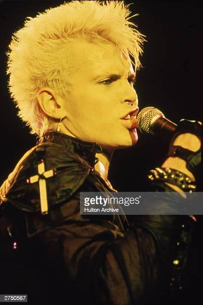 Headshot of British rock singer Billy Idol singing on stage circa 1985