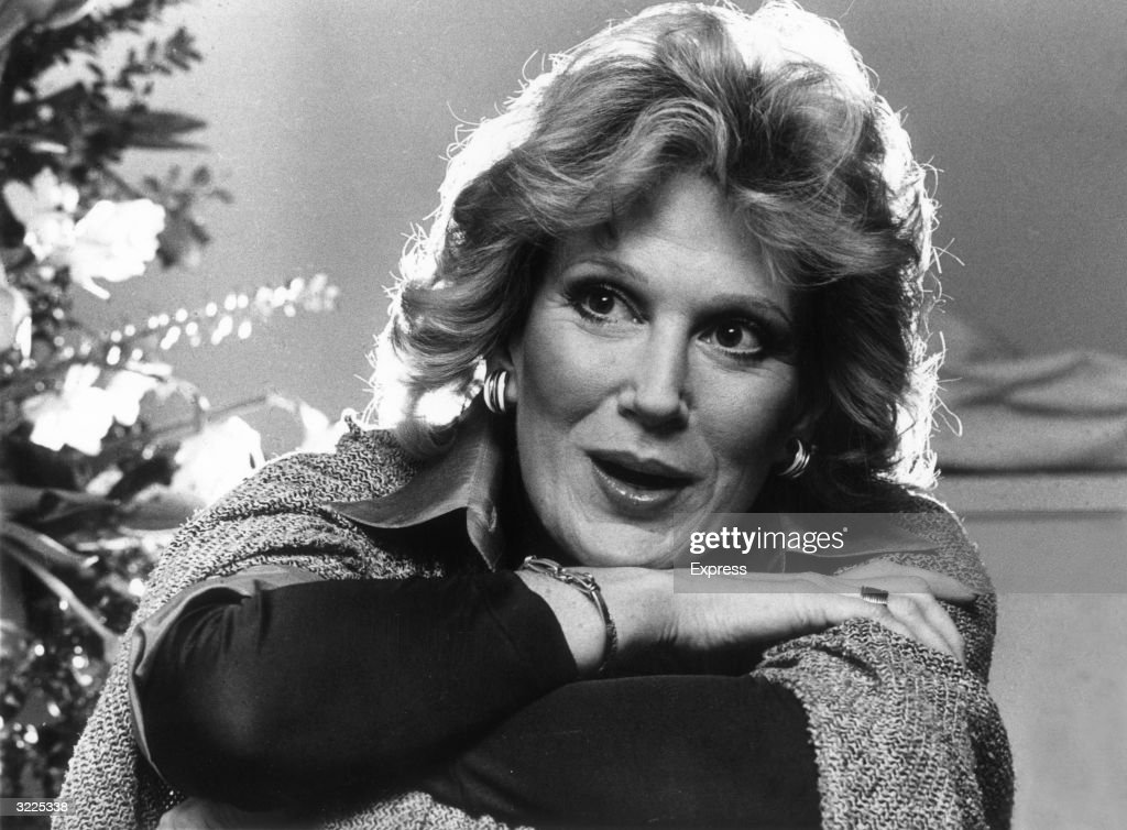 Headshot of British singer Dusty Springfield (1939 - 1999) smiling while resting her chin on her arms. She had just released her album, 'It Begins Again.'