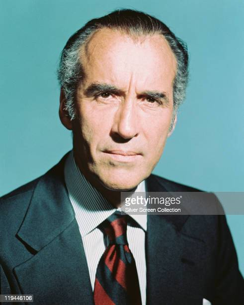 Headshot of Christopher Lee British actor wearing a redandblack striped tie in a studio portrait against a light blue background circa 1970