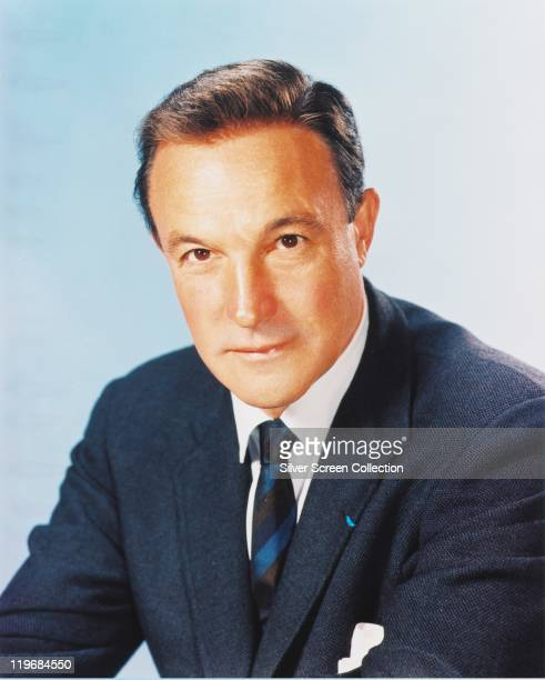 Headshot of Gene Kelly US actor and dancer wearing a dark blue jacket white shirt and blue striped tie in a studio portrait against a white...
