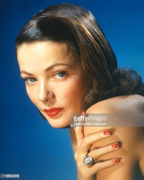 Headshot of Gene Tierney US actress in a studio portrait against a blue background circa 1940
