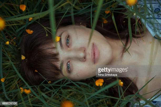 Headshot of girl laying down in green grass and yellow flowers